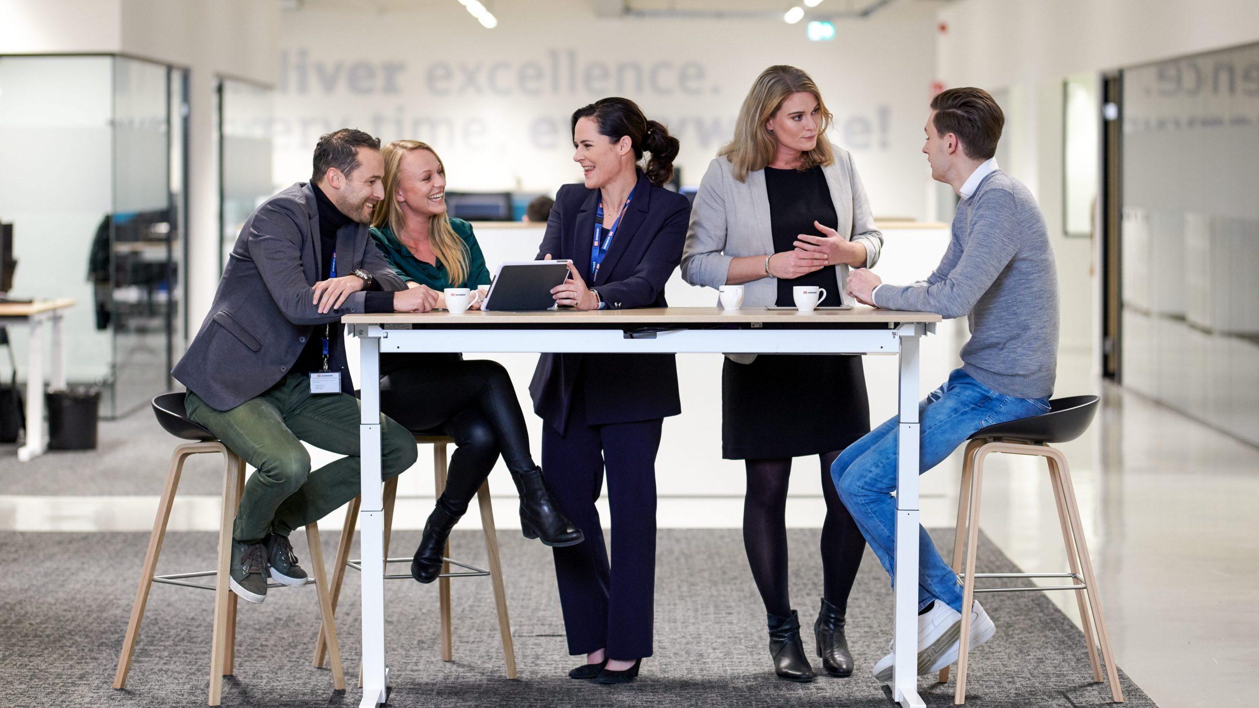 DB Schenker on kansainvälinen työpaikka. Henkilökuntaa keskustelemassa pöydän ääressä.